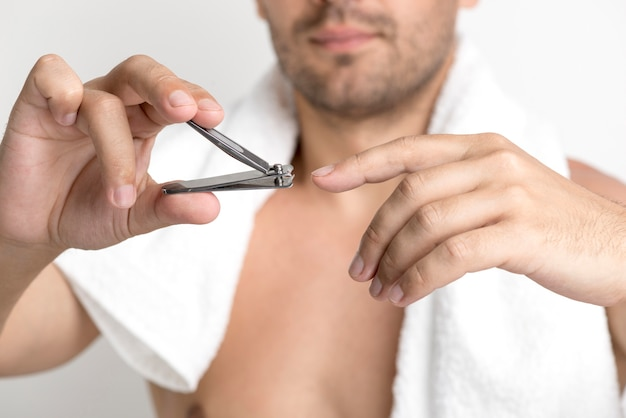 Close-up of man cutting his finger nails with nail clipper