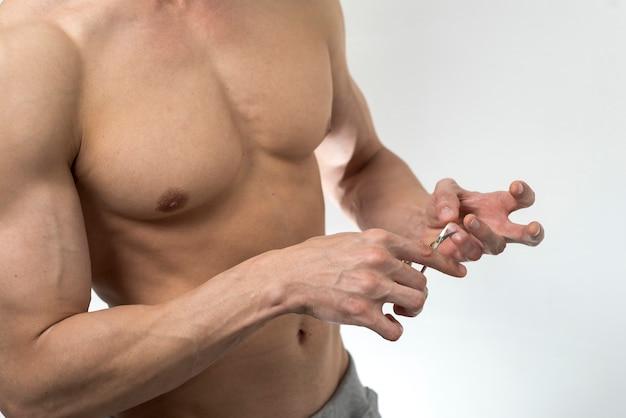 Крупным планом мужчина обрезает ногти