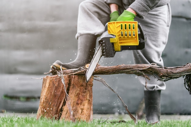 Close up of man cutting a log with a chainsaw in the garden leaning on another log on a sunny day
