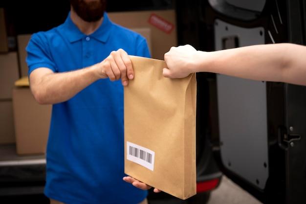 Primo piano uomo che consegna pacco delivering