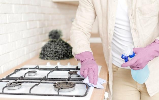 Close-up man disinfecting stove