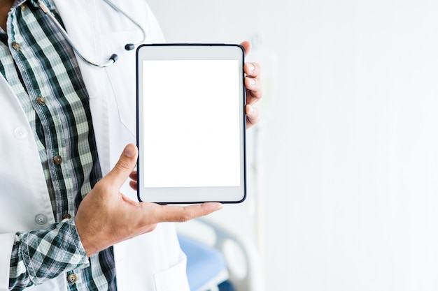 Close-up of man doctor therapeutic advising with positive emotions  holding up and showing digital tablet with a blank white screen and bed in hospital ,copy space