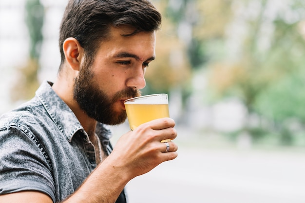 Close-up of man drinking glass of beer at outdoors