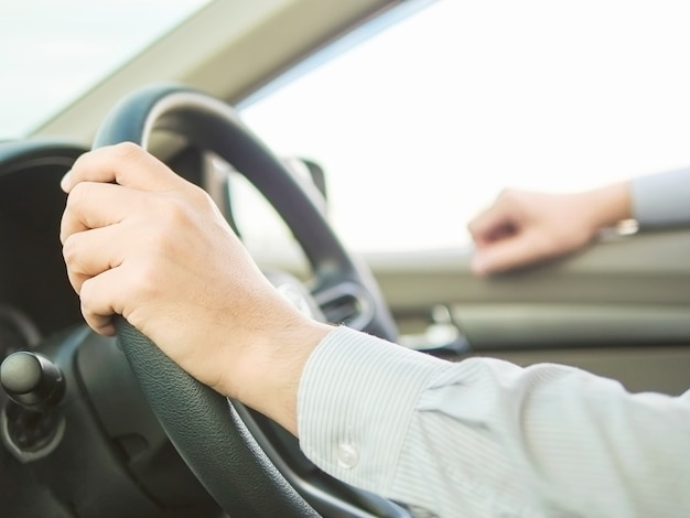 Chiuda su di un uomo che guida l'automobile facendo uso di una mano, comportamento pericoloso