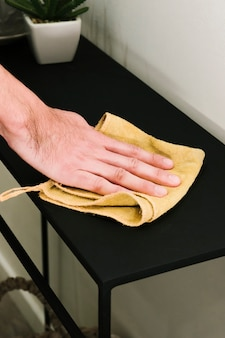 Close up man dusting table Free Photo