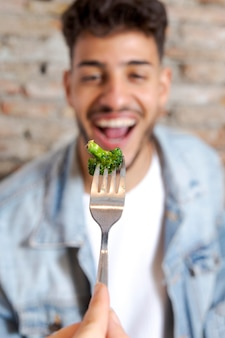 Close up man eating broccoli