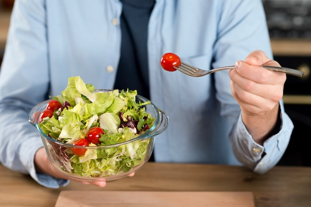 Close-up of a man eating the cherry tomato from salad in the glass bowl with fork