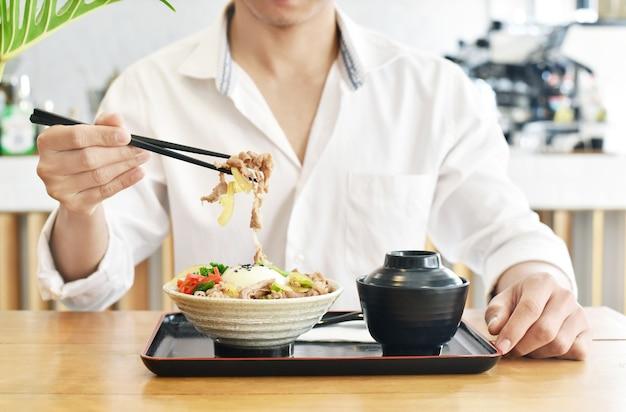 Крупным планом человек ест gyudon или японскую кухню из говядины