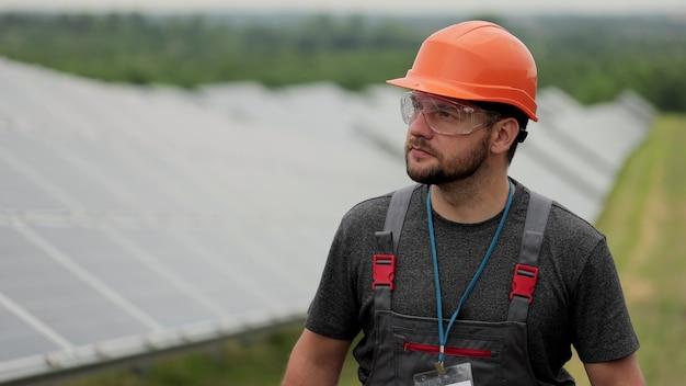 남자 에너지 기술자가 태양 전지판 분야를 걷고 광전지 태양 전지판을 검사합니다. concept.renewable 에너지, 기술, 녹색, 미래.