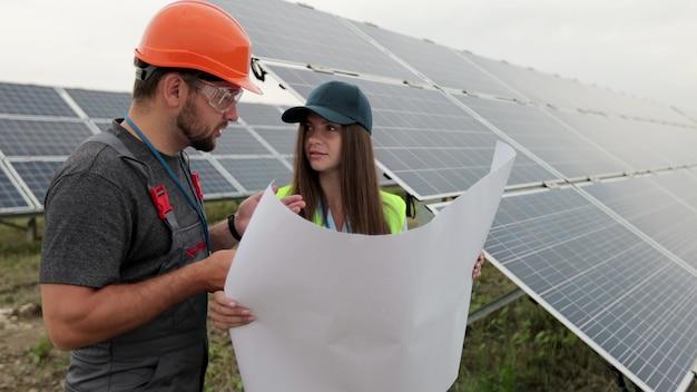단단한 모자를 쓴 남자 엔지니어와 태양 전지판의 종이 계획 건설을 배우는 조사관 엔지니어 여성을 닫습니다. 대체 에너지. 녹색 에너지의 개념입니다.