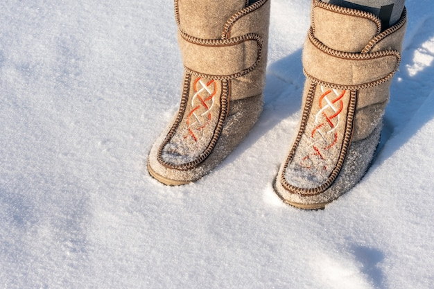 Close-up of a man in felt boots standing in the snow