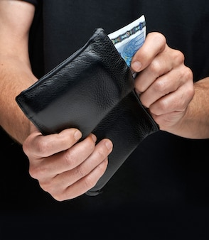 Close-up of a man getting a 20 euro bill out of the wallet