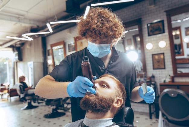 코로나바이러스 전염병 동안 마스크를 쓰고 이발소에서 머리를 자르는 남자를 닫아라. 장갑을 끼고 전문 이발사. 코비드-19, 아름다움, 자기 관리, 스타일, 건강 관리 및 의학 개념.