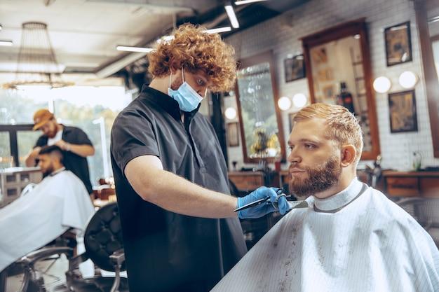 코로나 바이러스 전염병 동안 마스크를 쓰고 이발소에서 머리카락을 자르는 남자를 닫습니다.