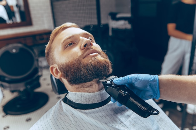 Primo piano uomo che si taglia i capelli dal barbiere che indossa la maschera durante la pandemia di coronavirus.