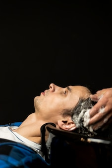 Close up man getting hairwashed with copy space