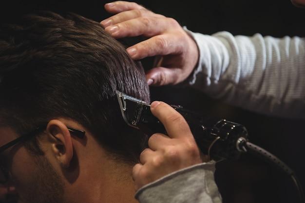 Primo piano dell'uomo che ottiene i suoi capelli tagliati con il rifinitore