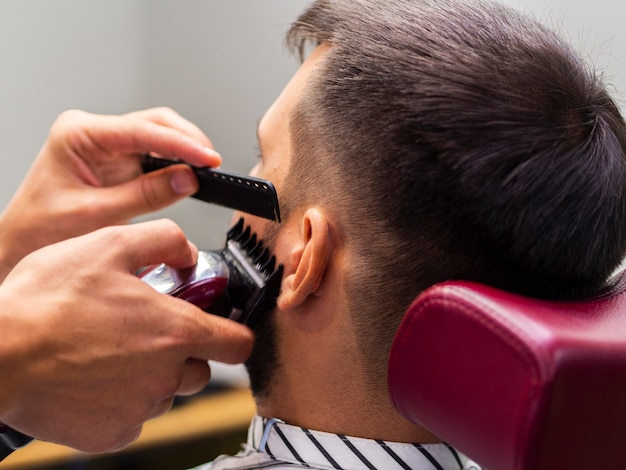 Close-up of man getting his sideburns cut from behind
