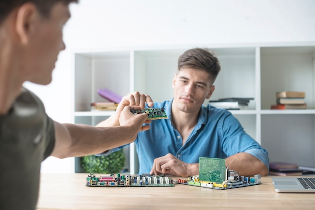 Close-up of man giving circuit board to his friend working with hardware equipment