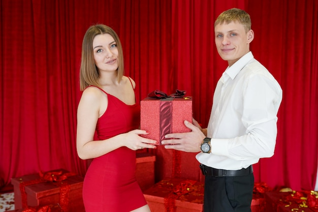 Close-up of man giving red giftbox to happy girl