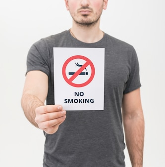 Close-up of man in gray t-shirt showing no smoking sign against white background