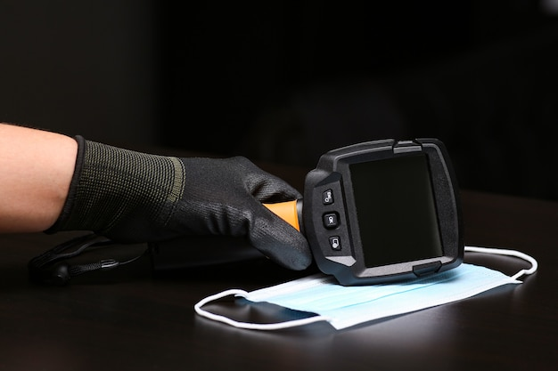 Close-up of a man hand-held in a glove holds a thermal imaging camera.