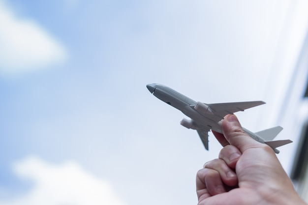Close up of man hand holding airplane toy and raise up to the sky