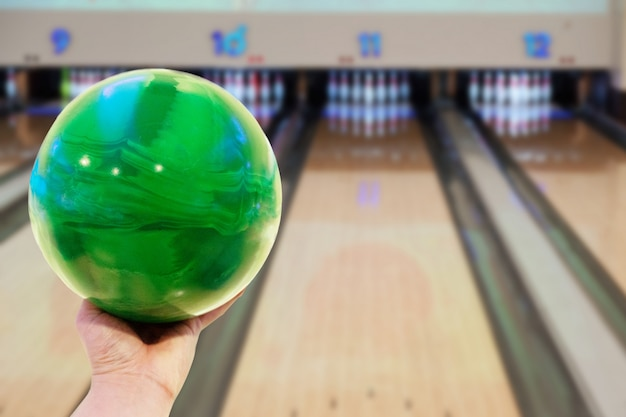 Close-up on a man hand holding bowling ball against bowling alley