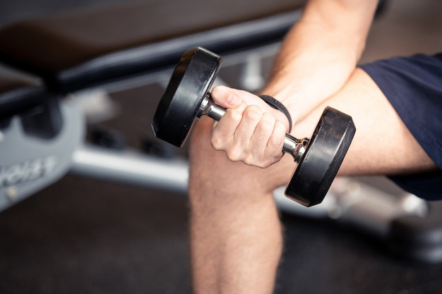 Close up of a man hand holding dumbbell at fitness gym