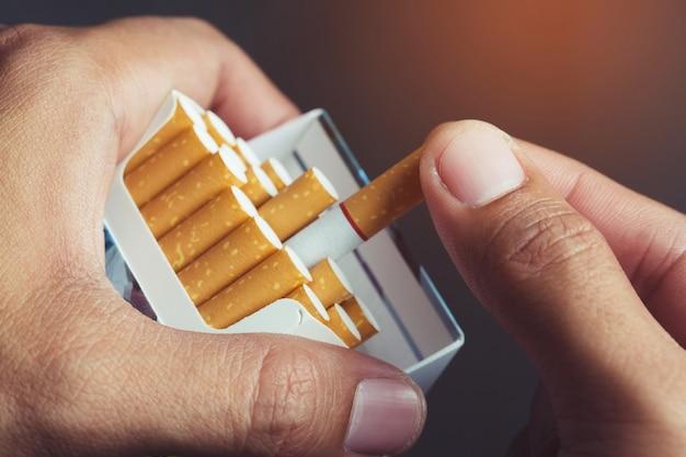 Закройте вверх по руке человека, держащего снимите его с пачки сигарет, подготовьте курить сигарету. линия упаковки.