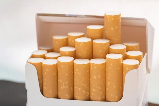 タバコのパックからそれをはがして持っている男の手を閉じて、タバコを吸う準備をします。