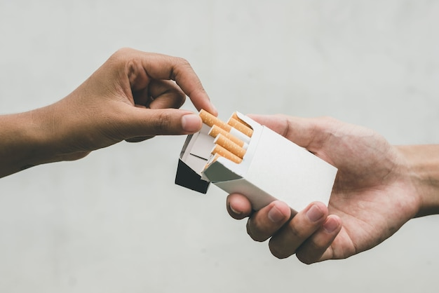 Close up man hand holding peel it off cigarette pack prepare smoking a cigarette. packing line up. cigarette smoke spread.