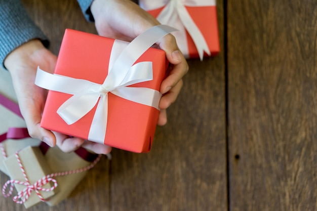 Close up man hand holding red gift box on wood deck for christmas concept
