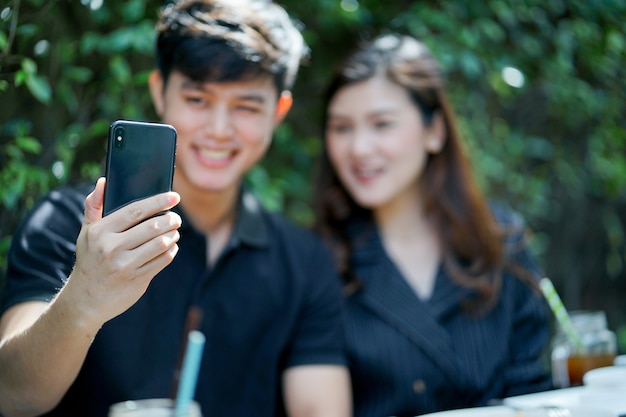 Close up on man hand holding smartphone to take photo (selfie) with girlfriends