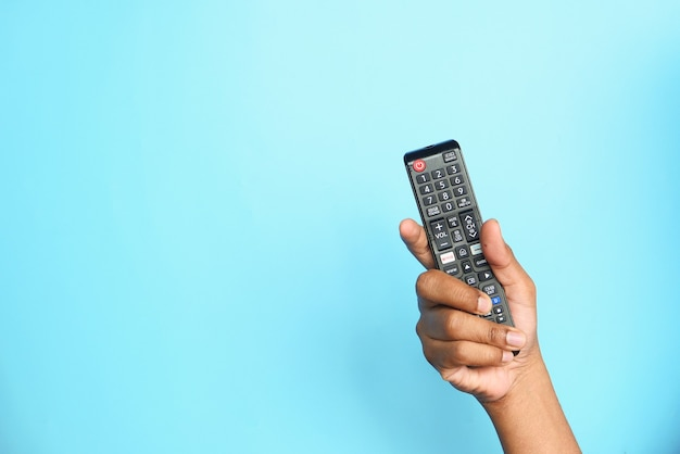 Close up of man hand holding tv remote on blue background