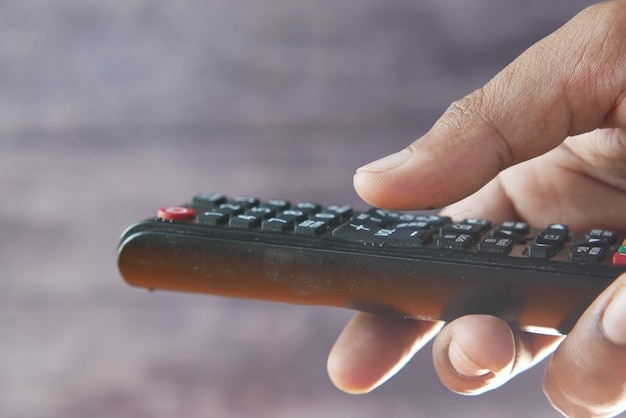 Close up of man hand holding tv remote