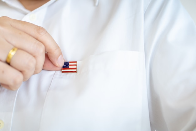 Close up of man hand holding united state of america nation flag pin on white shirt flag.