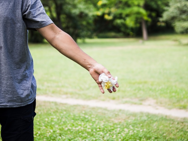 Close-up of man hand throwing crumpled paper in park