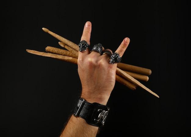 黒の背景、側面図上に2つの交差した壊れたバチを保持している悪魔の角ロックジェスチャーサイン、金属リングとブレスレットで男の手を閉じます。