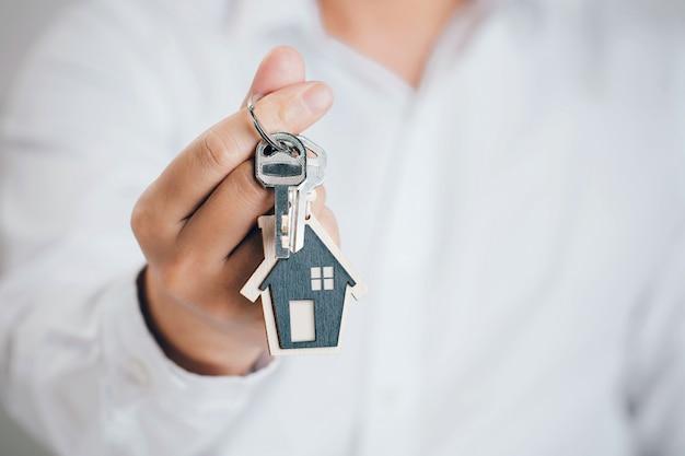 Закройте вверх человека, вручая ключ от дома. концепция покупки недвижимости