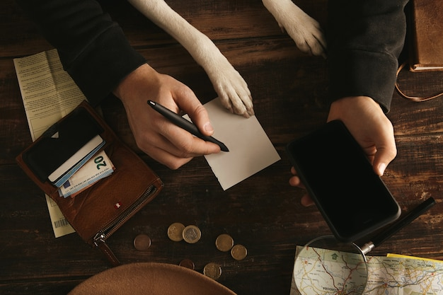 Close up man hands hold smartphone and writes adventure route plan in paper sheet on aged wooden table