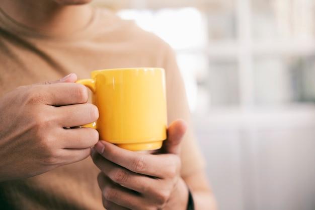 一杯のコーヒーを保持している男の手を閉じる