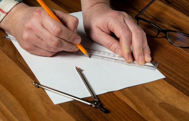 Close-up of man hands holding pencil and a ruler. working environment on the office table before creating a plan for or project