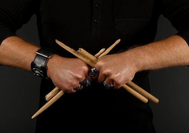 黒の背景、正面図上に2つの壊れた交差ドラムスティックを保持している男の手を閉じます。