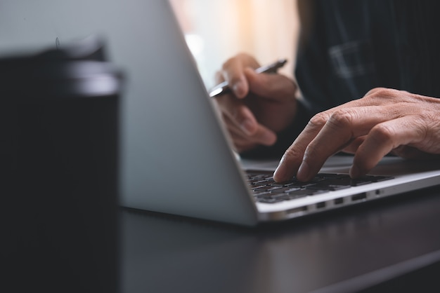 Close up of man hands typing on laptop computer on office table