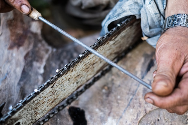 Close up man hands use a rasp to sharpen the blade chainsaw