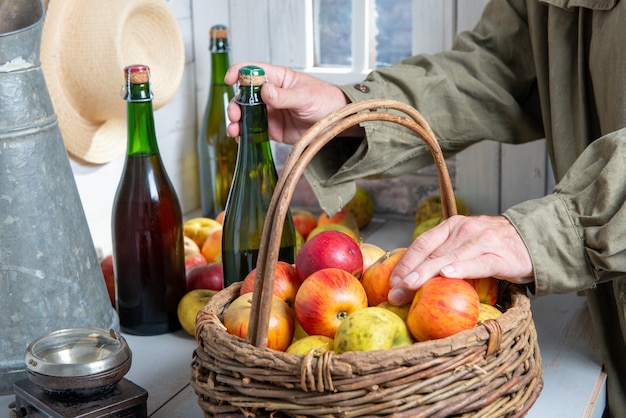 Close up of man hands with a bottle of cider and apples