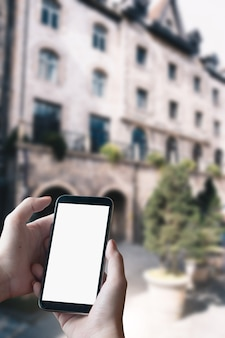 Close up of man hands with smartphone texting message on city street blurred background. blank screen for graphics display montage.