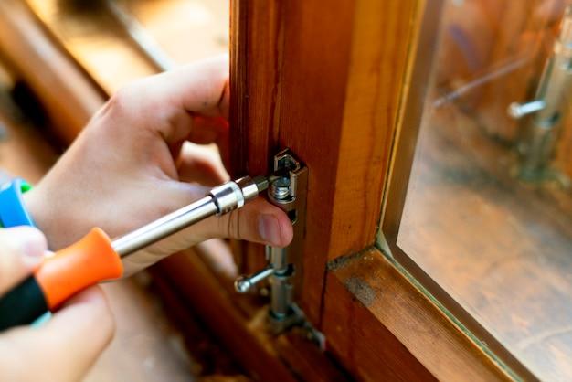 Закройте вверх руки человека работая регулирующ защелку стального болта на деревянном окне f