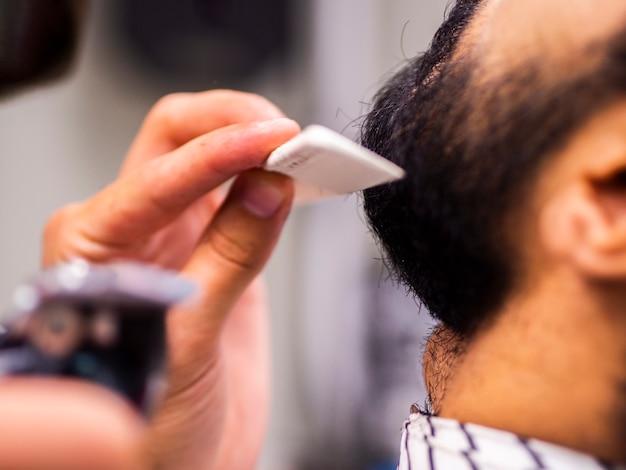 Close-up of man having his beard combed